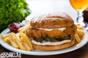 Sándwich de pollo frito con mayonesa y pepinillos