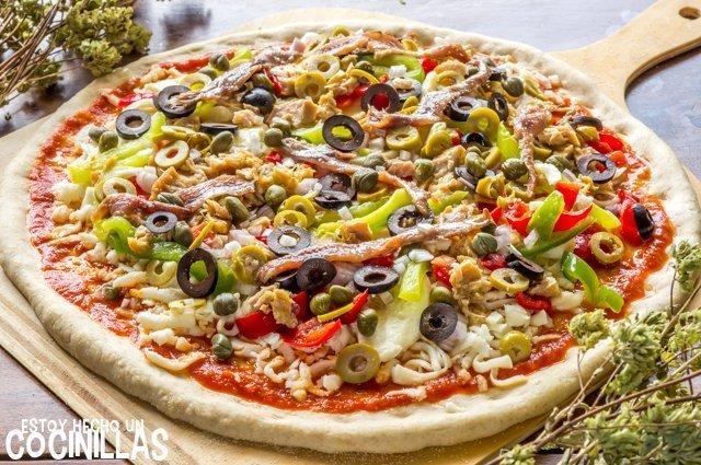Pizza de atún y anchoas con aceitunas (antes de hornear)