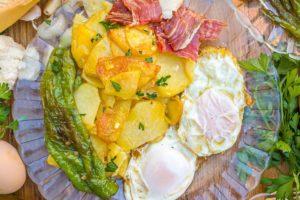 Huevos fritos con patatas, jamón y pimientos